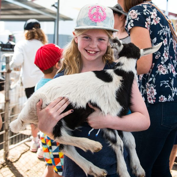 Girl wearing denim cap with peace symbol design carrying a baby goat